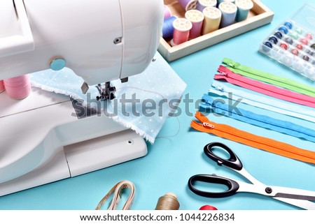 Pastel color background, Dressmaker and designer desk, Handcraft accessories, Threads roll, scissors, zip, button.