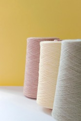 Pastel color bobbins of wool yarn for hand and machine knitting on a yellow background.