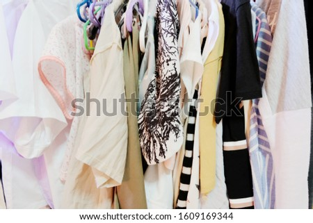 Pastel Color Female Clothes in a Row on Clothes Rail, closeup