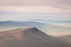 Pastel color palette of misty landscape with rocky mountain peak rising above fog covered valleys and mountain layers during colorful sunrise