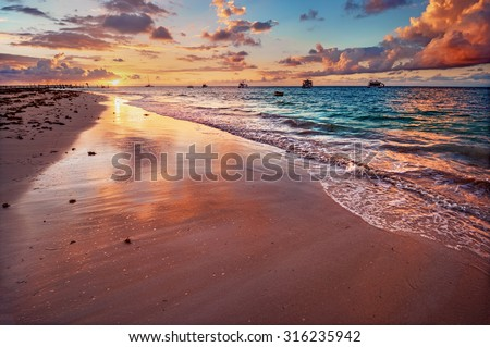 Stock Photo Pastel coloured sky and waters, at sunset, with boats in the background 2