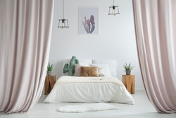 Pastel curtains in rustic bedroom with white rug and cacti on wooden stools next to king-size bed