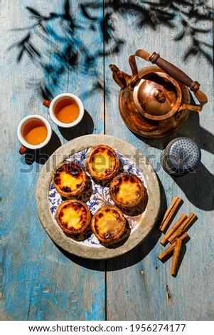 Pastel de Nata Fresh baked Portuguese egg custard Tart and Tea on blue wooden table Foto stock ©