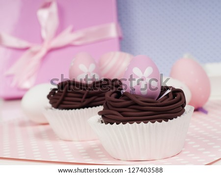pastel Easter decoration cupcakes with pink present in the background