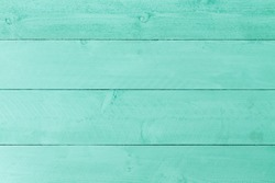 Pastel green stained wood background texture with horizontal parallel boards, woodgrain and copy space, full frame