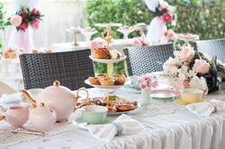 Pastel high tea set up featuring pastel pink, blue, yellow and green Royal Doulton tea set and an assortment of cupcakes, sweets and pastries.