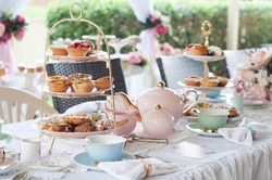 Pastel high tea set up featuring pastel pink, blue, yellow and green Royal Doulton tea set and an assortment of sweet and savoury pastries.