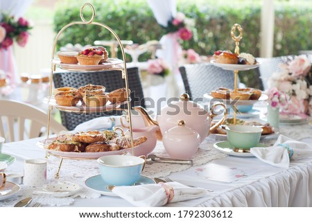 Pastel high tea set up featuring pastel pink, blue, yellow and green Royal Doulton tea set and an assortment of sweet and savoury pastries. Stockfoto ©