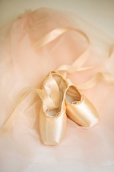 Pastel pink ballet shoes lie on background. New pointe shoes with satin ribbons lie on pink airy fabric, top view. You can use as poster or background.