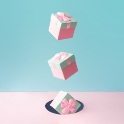 Pastel pink Christmas gift boxes on blue and pink backdrop. New Year present concept. Minimal composition.