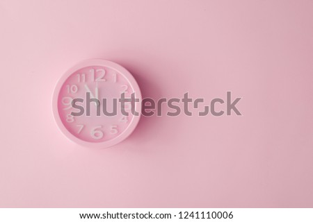 Pastel pink clock on pink painted wall. Minimal time concept. Chrismas eve or new year idea.