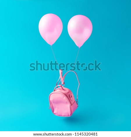 Pastel pink school bag with balloons floating against sky blue background. Surreal modern still life. Back to school minimal concept.
