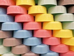 Pastel plastic bowls are placed in layers for background texture.