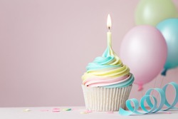Pastel rainbow birthday cupcake with candle and balloons