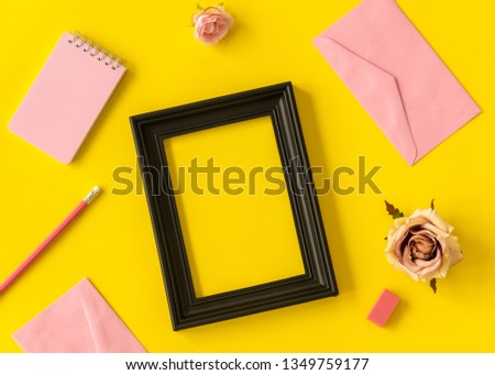 pastel space notebook and black picture frame with rose flower and pencil on yellow background