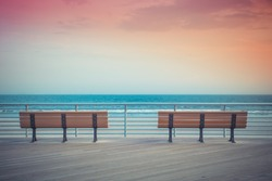 pastel toned beach boardwalk benches with ocean and sunset