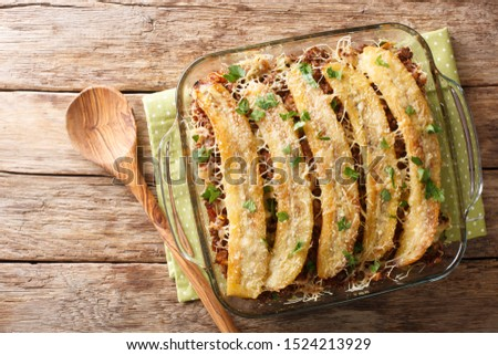 Pastelon de Platano Maduro is a close-up of banana lasagna in a baking dish on the table. Horizontal top view from above Foto stock ©