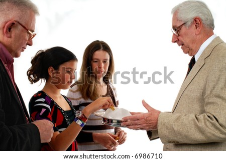 Pastor (or usher or elder) passing out communion bread. - stock photo