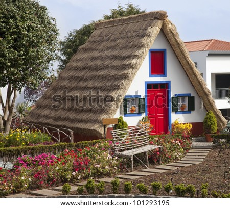 Pastoral landscape. Small rural house with a triangular thatched roof. The red door and small windows with shutters. Santana city, Madeira island,Portugal