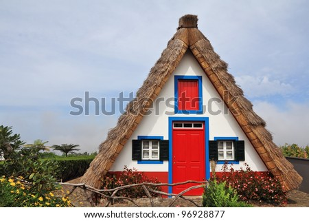 Pastoral landscape. Small rural house with a triangular thatched roof. The red door and small windows with shutters. Madeira, the city of Santana