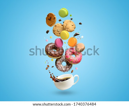 Pastries, confectionery and coffee cup with splash. Donuts, cookies, macaroons and coffee cup flying over blue background. Patisserie shop.