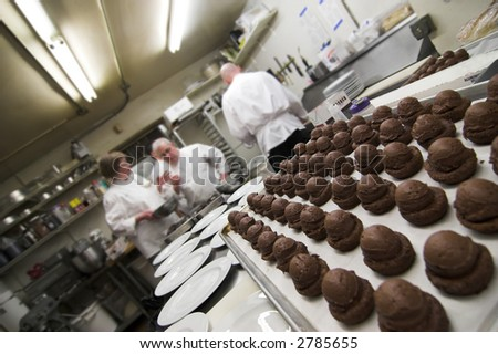 pastries in a restaurant kitchen with chefs in background