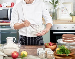 Pastry bakery chef in the kitchen preparing cake. bakery and food concept.