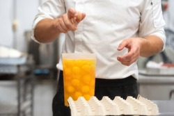 Pastry Chef breaking eggs to prepare the cake .