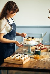 Pastry chef in the kitchen decorating a cake of chocolate,fruit,candies,Confectioner is decorating chocolate cake,cooking class, culinary, bakery, food and people concept