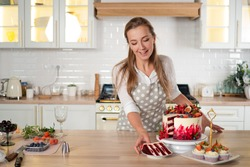 pastry chef in the kitchen makes desserts, cakes and muffins. Cooking at home. Delicious and beautiful homemade cakes, pastry recipes. A young woman in an apron in the kitchen made a red velvet cake