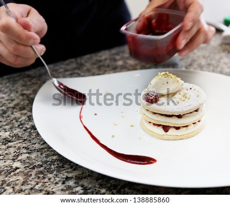 Pastry chef is decorating the dessert with red berry sauce