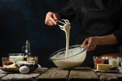 Pastry chef kneads a dough with a whisk. Backstage of cooking waffle on rustic wooden table with ingredients on dark blue background. Frozen motion. Handmade dessert. Cooking process.