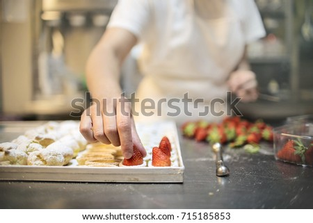 Pastry chef making pastries with cream and fruits #715185853