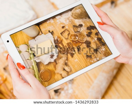 Pastry cooking vlog. Lady using tablet to record steps of cooking gingerbread biscuits. Ingredients on screen.