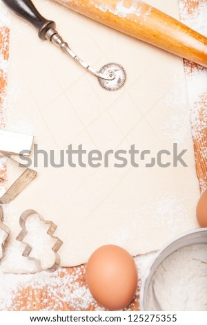 pastry, rolling pin, eggs and figures for cookies on wooden