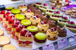 Pastry shop with variety of donuts, muffins, creme brulee, cakes with fruits and berries