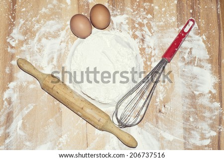 Pastry utensils: eggs, flour, whisk and rolling pin.