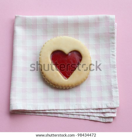 Pastry with jam heart on a napkin