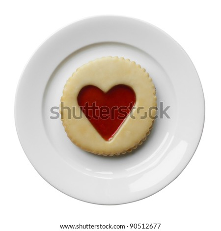 Pastry with jam heart on a plate isolated on white