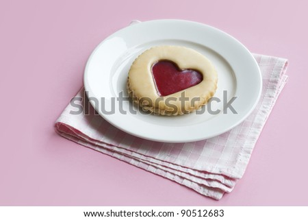 Pastry with jam heart on a plate on pink background