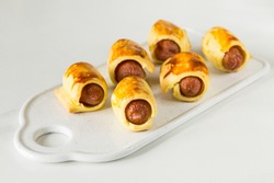 Pastry wrapped sausage rolls, fried sausage pies in dough. Junk food concept