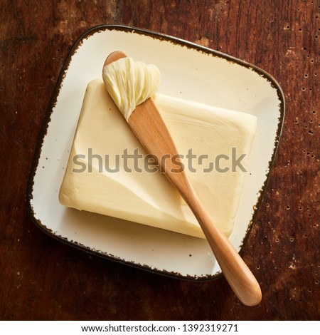Pat of farm butter with wooden spreader with a scoop of butter on top viewed from above on a rustic wood table in square format