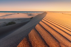 Patara beach is a famous tourist landmark and natural destination in Turkey. Majestic view of orange sand dunes and hills glows in the rays of the warm sunset.