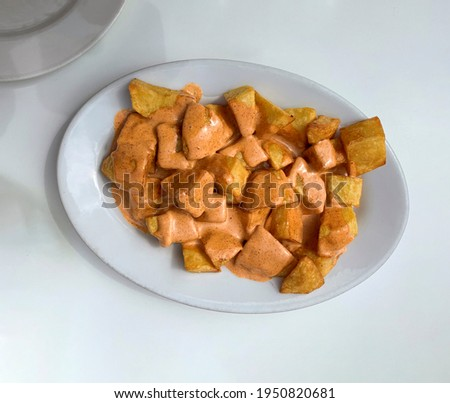 Patatas a la brava or papas bravas, are potatoes cut into irregular cubes of approximately three centimeters in size and that are fried in oil and accompanied by a sauce. Photo stock ©