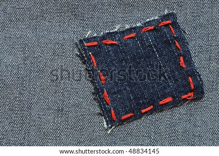 Patch with red thread attached on jeans textured