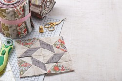 Patchwork block on craft mat, rolls of fabric, sewing accessories on white wooden surface