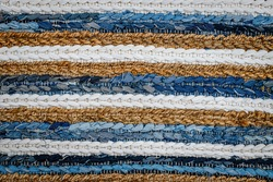 Patchwork rug from denim jeans fabric, top view. Recycle old jean denim floor mat, door mat, area rug. Recycling motley striped cloth carpet. Zero waste concept. Boho style background. Cozy home.