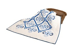 Patchwork white-blue quilt on a white background. Patchwork blanket. Handmade. Patchwork quilt on a white background.