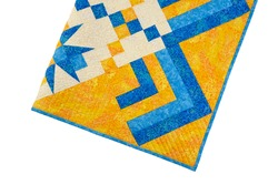 Patchwork yellow-blue quilt on a white background. Patchwork blanket. Handmade. Patchwork quilt on a white background.