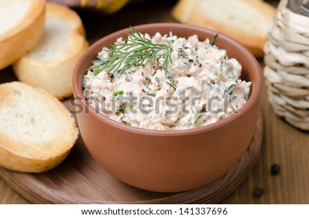 pate of smoked fish with sour cream and herbs on a wooden board, close-up